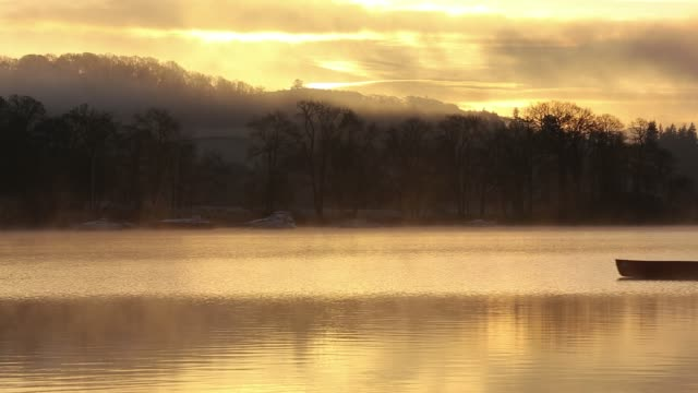 Mist at dawn over Lake Windermere, Lake District, UK, with a man in a Canadian Canoe.