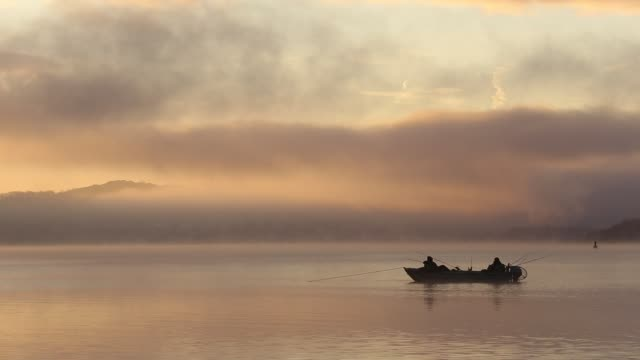 mist at dawn over lake windermere, lake district, uk, with two fisherman in a boat. - recreational boat stock videos & royalty-free footage