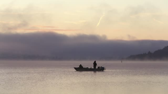vídeos de stock e filmes b-roll de mist at dawn over lake windermere, lake district, uk, with two fisherman in a boat - embarcação de lazer
