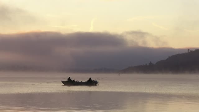 mist at dawn over lake windermere, lake district, uk, with two fisherman in a boat and a passing canadian canoe - silence stock videos & royalty-free footage