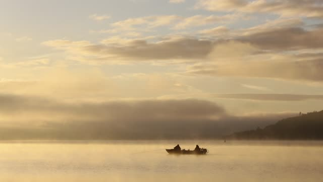 mist at dawn over lake windermere, lake district, uk, with two fisherman in a boat - small boat stock videos & royalty-free footage