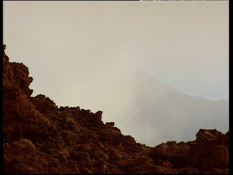 mist clears to show volcanic mountain with rocky foreground pico de teide - isole dell'oceano atlantico video stock e b–roll