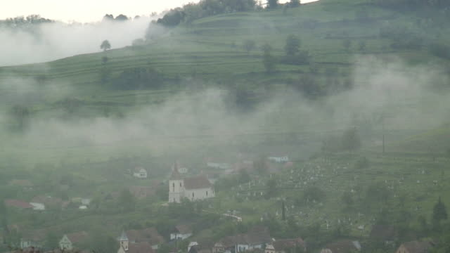 ha ws mist covering church and village cemetery in valley / biertan, sibiu, romania - romania stock videos & royalty-free footage