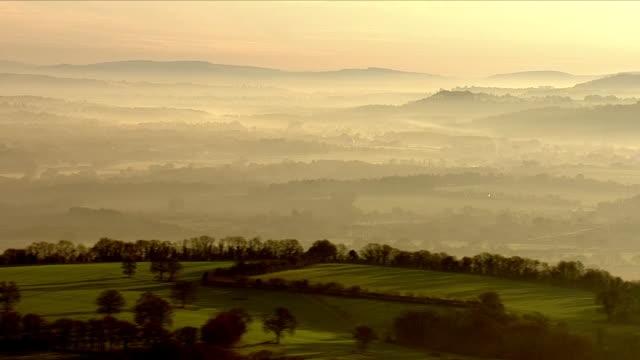 mist covering green countryside - alba crepuscolo video stock e b–roll