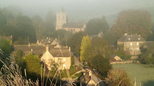 ha ws mist covering village in early morning in autumn / naunton, gloucestershire, england - english culture stock videos & royalty-free footage