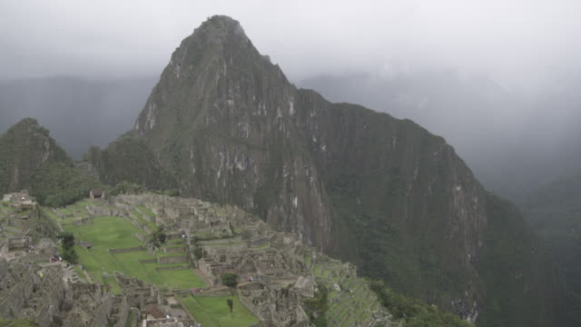 mist covers a mountainside in machu picchu. - machu picchu stock videos and b-roll footage