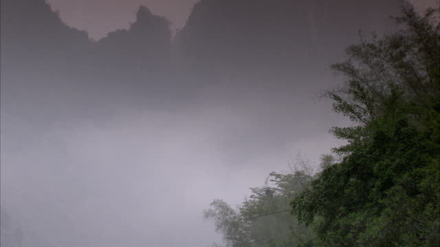 vídeos de stock, filmes e b-roll de mist covers forested mountains in china. available in hd. - árvore de folha caduca