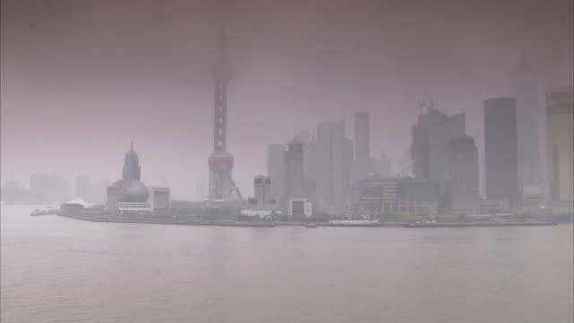A mist covers the Huangpu River and skyscrapers in Shanghai, China. Available in HD.