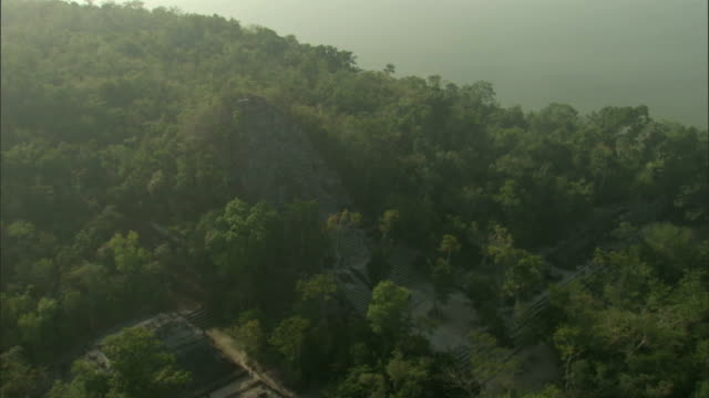 mist obscures mayan ruins in a yucatan jungle. available in hd. - civiltà maya video stock e b–roll