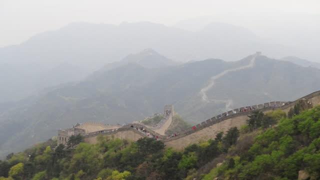 vídeos y material grabado en eventos de stock de a mist obscures mountains as tourists visit the great wall at badaling. - badaling