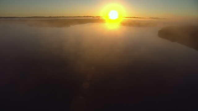 WS AERIAL POV Mist over river, sun rising in background / Dane County, Wisconsin, United States