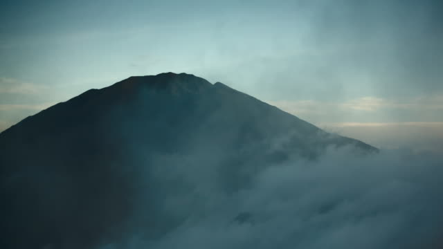 Mist peels away to reveal summit of volcano, Mount Merapi, at dawn.  Indonesia