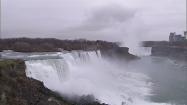 mist rises from niagara falls. - niagara falls stock videos and b-roll footage