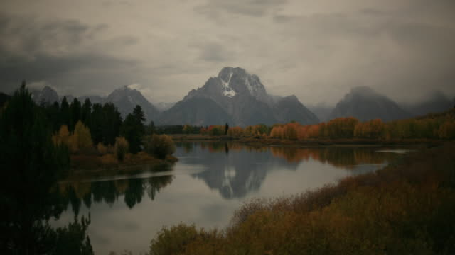mist rises from snake river and forest as stars wheel over mountains, golden full moon sinks behind mount moran.. - mt moran stock videos & royalty-free footage