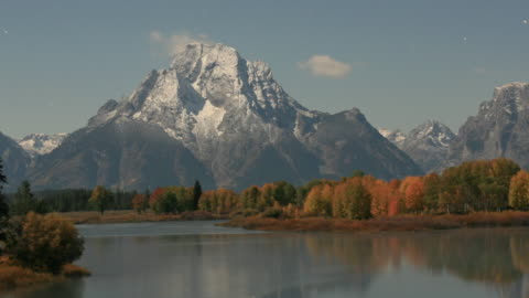 mist rises from snake river and forest as stars wheel over mountains, golden full moon sinks behind mount moran.. - teton range stock videos & royalty-free footage