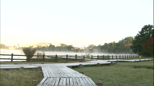 Mist rises from the pond and frost covers the boardwalk in Morioka Takamatu Park, Japan.