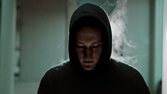 slo mo mist rising behind a young man in a hood - hooded top stock videos & royalty-free footage