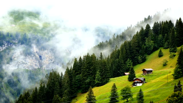 mist rising over swiss cottage in the alps - remote location stock videos & royalty-free footage