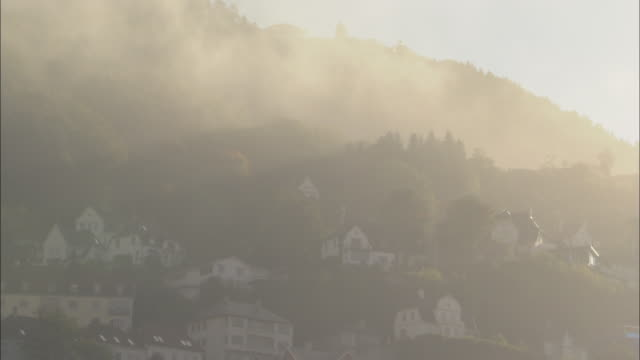 Mist shrouds the hillside houses in Bergen.
