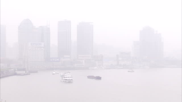 a mist surrounds skyscrapers on the bank of the huangpu river in shanghai, china. available in hd. - river huangpu stock videos & royalty-free footage