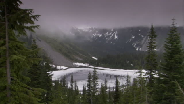 a mist swirls over an icy lake in the mountains. - evergreen stock videos & royalty-free footage