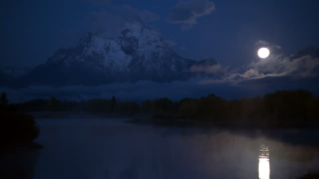 mist swirls over moonlit mountain lake at night, yellowstone, usa - full moon stock videos & royalty-free footage