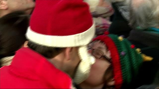 vídeos de stock, filmes e b-roll de 'mistletoe kisses' event at borough market people gathered for event under mistletoe / people countding down sot / people kissing / ribbons and... - trepadeira