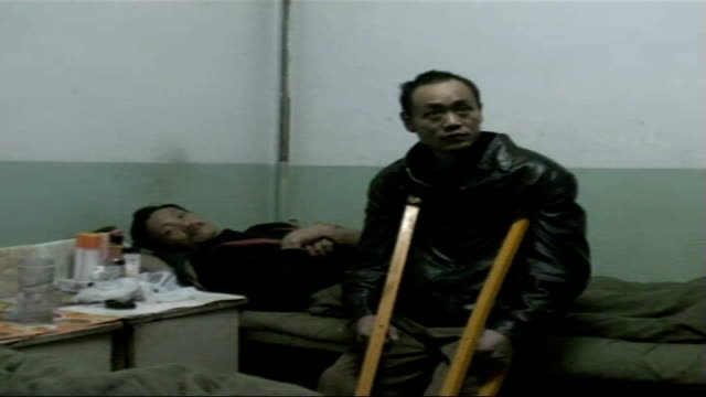 mistreatment of coal miners man using crutches leaning against hospital bed where another male patience lies face of maimed coal miner - 発電所関係の職業点の映像素材/bロール