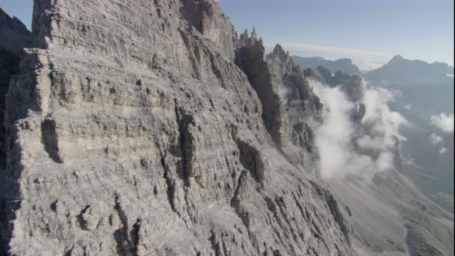 Misty clouds drift past rugged pinnacles of the Italian Dolomites. Available in HD.