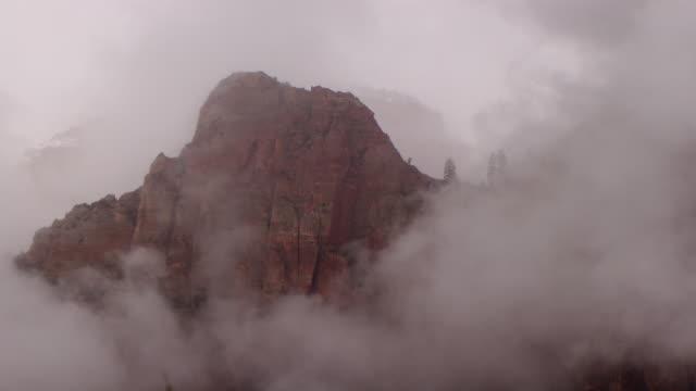 misty gray clouds swirling around rocky mountain peak - ザイオン国立公園点の映像素材/bロール