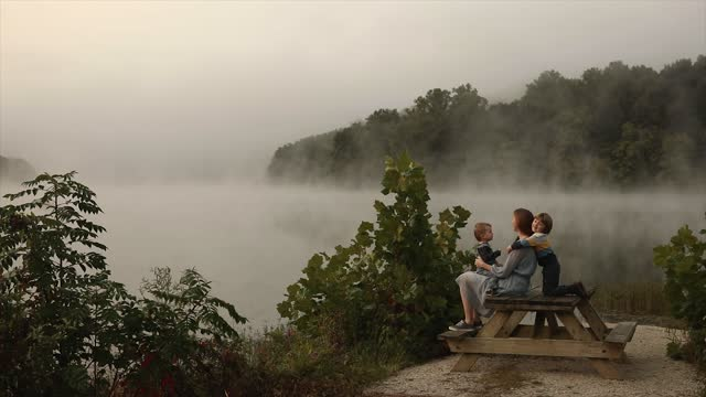 misty lake in early morning on wood bench with children - lake stock videos & royalty-free footage