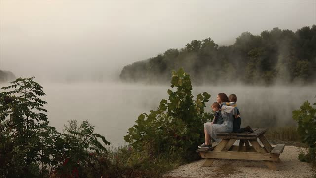 misty lake in early morning with children on bench - lake stock videos & royalty-free footage