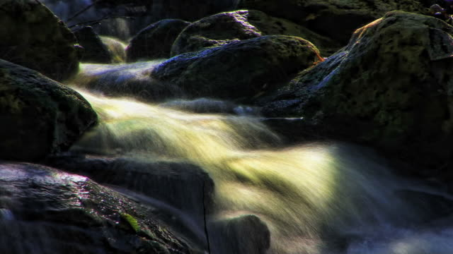 misty waters flow through giant rocks. - digital enhancement stock videos and b-roll footage