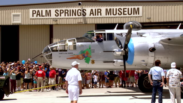 ws pan zo wwii b25 mitchell bomber plane slowly pulls out of air hangar with thousands of  memorial day  spectators watching from behind roped off area / palm springs, california , united states - roped off stock videos and b-roll footage