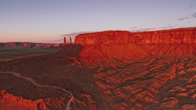 aerial mitchell mesa in der frühen morgensonne im monument valley, usa - tafelberg felsformation stock-videos und b-roll-filmmaterial