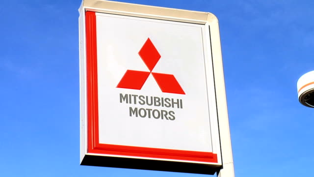 Mitsubishi roadside sign ZOWS new cars parked on dealer lot / CU Mitsubishi roadside sign ZOWS new cars parked in front of dealership building / WS...