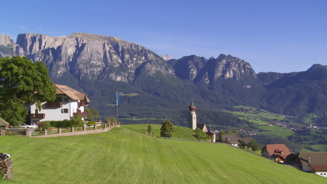 pan mittelberg village on ritten (renon) plateau in front of mount schlern (sciliar) in south tyrol - motion controlled shot - sciliar schlern video stock e b–roll