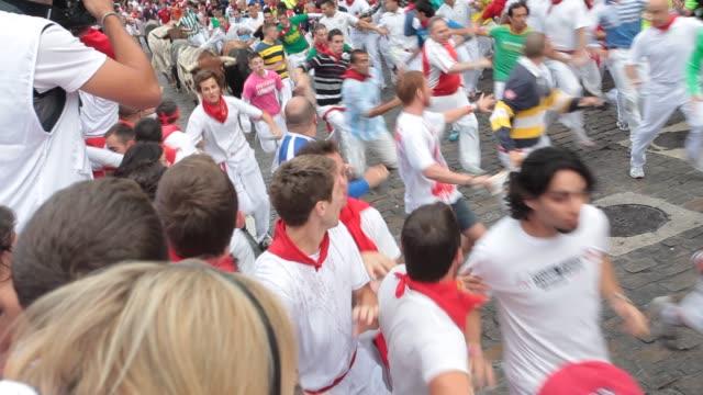miura bulls run along with the crowd towards the end of the encierro during san fermin celebration in pamplona on july 8, 2012. fiesta de san fermin... - human interest stock videos & royalty-free footage