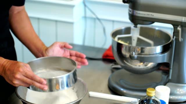vidéos et rushes de mélanger les ingrédients du gâteau - une seule femme d'âge moyen