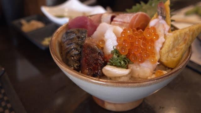 魚の刺身をご飯と混ぜる。和食スタイル、ヘルシーフードコンセプト - 高級グルメ点の映像素材/bロール