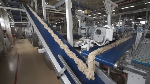 vídeos de stock, filmes e b-roll de mix for tuc biscuits moves along a conveyor belt before baking at the trostyanets confectionery plant, operated by mondelez international inc., in... - doces
