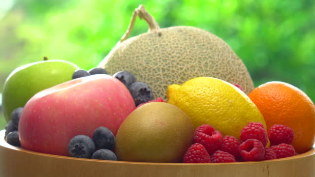 mix fruit in wooden bowl rotating on blur lush foliage background - fruit bowl stock videos & royalty-free footage