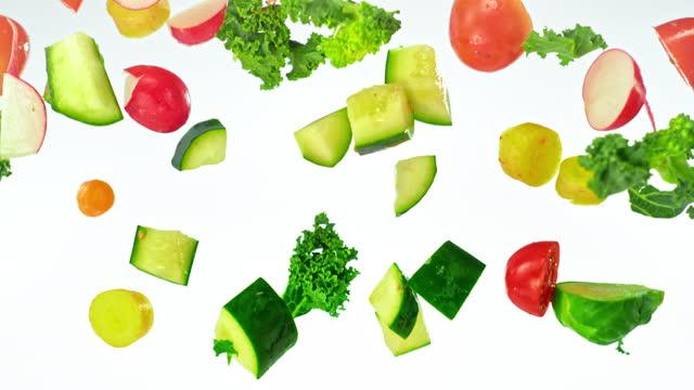 vidéos et rushes de slo mo ld un mélange de légumes coupés tombant - fond blanc