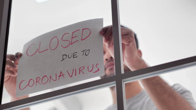 a mix race person business owner puts a closed sign on the front door due to the coronavirus covid19 pandemic.information sign, small business, lockdown, unexpected, conquering adversity, challenge, covid-19 business signage - unemployment stock videos & royalty-free footage
