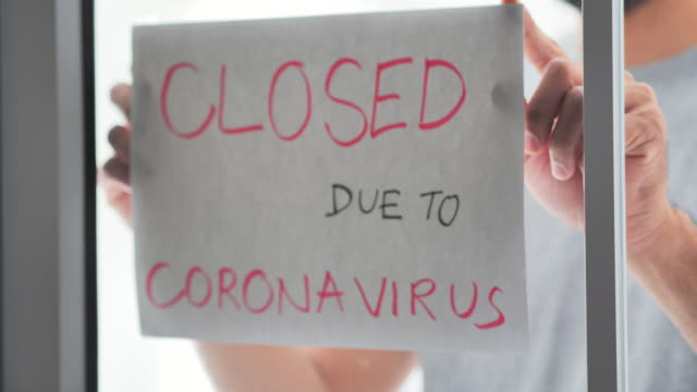 a mix race person business owner puts a closed sign on the front door due to the coronavirus covid19 pandemic.covid-19 business signage - information sign stock videos & royalty-free footage