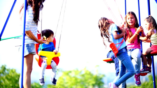 mixed age children having fun on a swing set. - playground stock videos and b-roll footage
