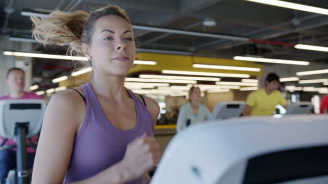 mixed age group of latin american people at the gym exercising on different machines - cross trainer stock videos & royalty-free footage