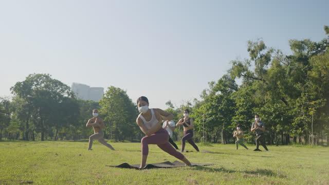 vídeos y material grabado en eventos de stock de grupo mixto de edad de personas que hacen ejercicios de poses de yoga al aire libre usando máscaras de protección médica - concepto de vida durante o después de la cuarentena, medidas de protección contra coronavirus - pilates