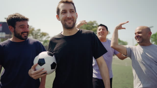 mixed age range group of men celebrating success on soccer field - mixed age range stock videos & royalty-free footage