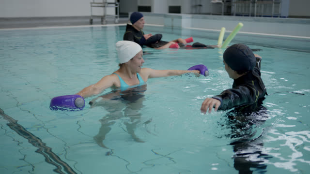 mixed age range group of patients and therapist doing exercises during hydrotherapy at a physical rehab clinic - mixed age range stock videos & royalty-free footage